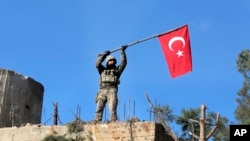 FILE - A soldier waves a Turkish flag as Turkish troops secure Bursayah hill, which separates the Kurdish-held enclave of Afrin from the Turkey-controlled town of Azaz, Syria, Jan. 28, 2018.