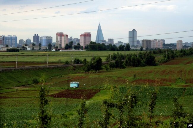 FILE - The Pyongyang skyline, stands in the background of some agricultural land on the outskirts of Pyongyang, North Korea, June 15, 2018.