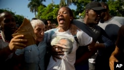 A member of the dissident group, Ladies in White, is detained by Cuban security before the start of a march marking International Human Rights Day in Havana, Cuba, Tuesday, Dec. 10, 2013.