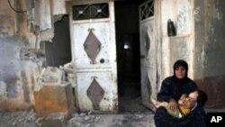 Một phụ nữ bế con ngồi trước căn nhà đã bị đổ nát của bà