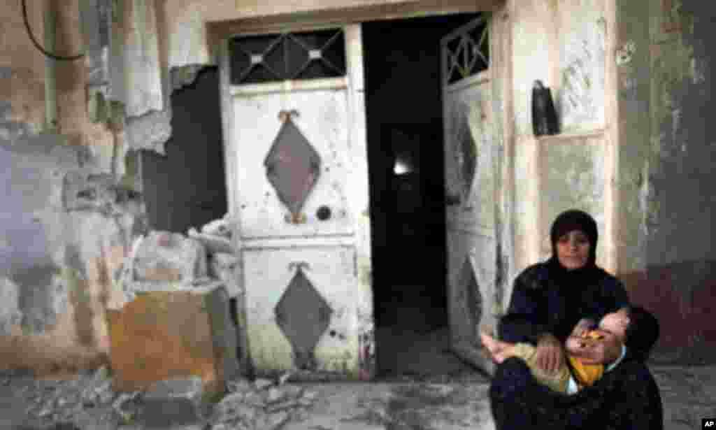 Жінка з дитиною біля знищеного будинку у Тремсех, Сирія.