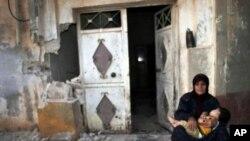 Suriyalik ona va bola Tremsa qishlog'ida vayron bo'lgan uyi yonida, 14-iyul, 2012-yil.