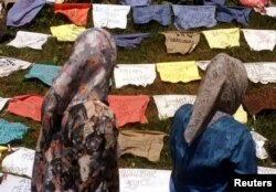 FILE - Refugee women read the names of missing men written on pillows July 18 at the site near the Bosnian town of Kladanj where Muslims from Srebrenica crossed the former front line three years ago escaping from Bosnian Serb forces, July 11, 1995.