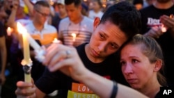 FILE - People hold candles during a vigil downtown for the victims of a mass shooting at the Pulse nightclub in Orlando, Florida, June 13, 2016.