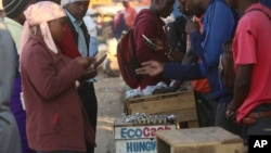 FILE: In this photo taken Thursday, Aug. 8, 2019, vendors are seen on their mobile phones while selling cash at a premium in Harare, Zimbabwe. With inflation soaring and cash in short supply, many Zimbabweans transfer funds using their mobile phones.