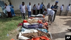 Somalis observe bodies that were brought to and displayed at a Mogadishu hospital, Aug. 25, 2017.
