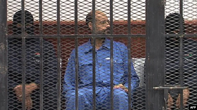 FILE - Saif al-Islam Gadhafi in the accused cell as he stands trial for illegally trying communicating with the outside world in June of 2012, Zintan, Libya, May 2, 2013.