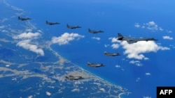 This picture provided by the SOuth Korean Defense Ministry shows a US Air Force B-1B Lancer bomber (R), US F-35B stealth jet fighters (bottom) and South Korean F-15K fighter jets (top) flying over South Korea during a joint military drill aimed to counter North Korea's latest nuclear and missile tests. The US flew four stealth fighter jets and two bombers over the Korean peninsula on September 18 (Credit: AFP PHOTO / South Korean Defence Ministry handout).