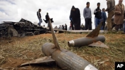 People look at components of AIM-9 Sidewinder air-to-air missiles from a U.S Air Force F-15E fighter jet after it crashed near the eastern city of Benghazi March 22, 2011