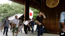 Seorang pengunjung membungkukkan badan untuk menghormati para pahlawan yang gugur dalam perang, saat pengunjung lainnya memasuki Tugu Yasukuni di Tokyo, Senin (15/8).