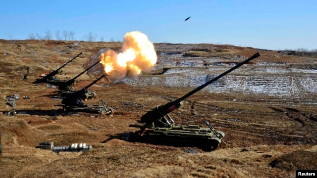 FILE - North Korea's artillery sub-units, whose mission is to strike Daeyeonpyeong island and Baengnyeong island of South Korea, conduct a live shell firing drill to examine war fighting capabilities in the western sector of the front line in this picture
