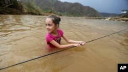 Ruby Rodriguez, 8, looks back at her mother as she wades across the San Lorenzo Morovis river with her family, since the bridge was swept away by Hurricane Maria, in Morovis, Puerto Rico, Sept. 27, 2017. They were returning to their home after visiting family.