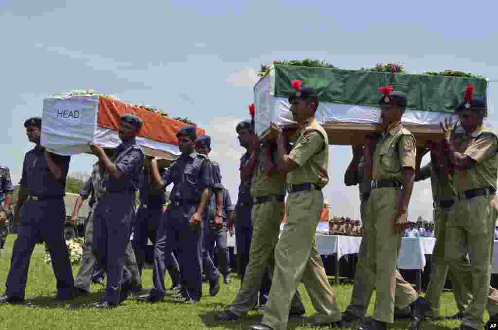 Indian security officers carry coffins containing victims of a helicopter that crashed during a rescue mission in flood-ravaged northern India, in Dehradun, India. The air force helicopter hit the side of a mountain and fell into a river on Tuesday, killing five crew members and three civilians on board.