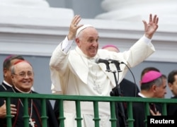 FILE - Pope Francis gestures while addressing the crowd from the Cathedral of Our Lady of the Assumption in Santiago, Cuba, Sept. 22, 2015.