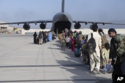 افغانستان چھوڑنے کے خواہش مند افراد کو طیارے میں سوار کرایا جا رہا ہے۔ 22 اگست 2021