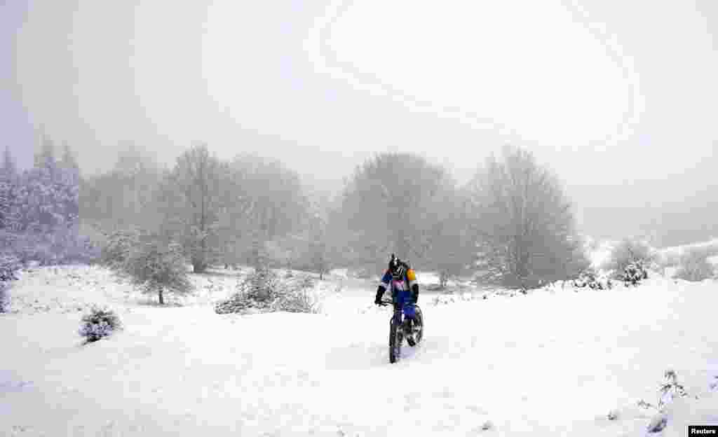A cyclist rides his bike across a snow-covered field in the Basque mountain port of Opakoa, northern Spain.