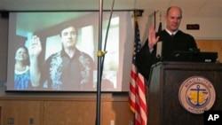 Walikota Anchorage, Dan Sullivan didampingi istrinya Lynette yang sedang berlibur di Hawaii, diambil sumpah jabatannya melalui saluran video jarak jauk (terlihat dalam layar televisi) oleh Hakim Brian Clark (kanan) yang berada di Alaska (2/7).