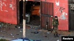 A Lebanese Army soldier guards a cafe where a suicide bomb attack took place in Jabal Mohsen, Tripoli, Jan. 11, 2015.