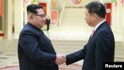 Северокорейский лидер Ким Чен Ын (слева) приветствует главу международного отдела Компартии Китая Сун Тао. Пхеньян. Фото опубликовано 15 апреля 2018 г.