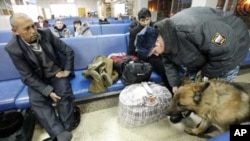 A police officer with a sniffer dog checks a passenger's luggage at the Yemelyanovo airport near Russia's Siberian city of Krasnoyarsk, Jan 26, 2011