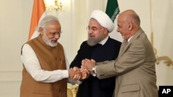 Dari kiri: PM India Narendra Modi, Presiden Iran Hassan Rouhani, dan Presiden Afghanistan Ashraf Ghani saling berjabat tangan pasca penandatanganan kerjasama di Teheran, Senin (23/5).