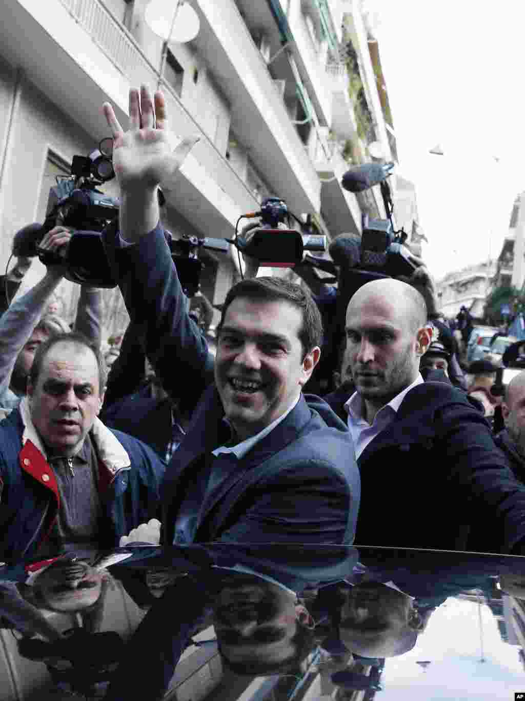 Alexis Tsipras, leader of Greece's Syriza left-wing main opposition waves to his supporters after voting at a polling station in Athens, Jan. 25, 2015.