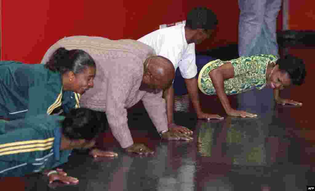 Первая леди США отжимается от пола вместе с архиепископом Десмондом Туту (третий справа) во время мероприятия по повышению информированности и профилактике ВИЧ в Кейптауне. 23 июня 2011г.