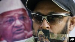 A supporter of veteran Indian social activist Anna Hazare is seen with a photo of Hazare over his mouth during a protest rally against corruption in the northern Indian city of Chandigarh Aug. 17, 2011.