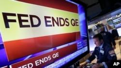 紐約證券交易所內的電視屏幕2014年10月29日消息顯示美國聯邦儲備局決定停止執行量化寬鬆政策 (AP)