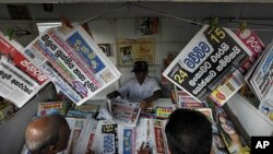 "People stand in front of a newspaper stall, as headlines read, from left top, ""Operation unsuccessful,"" ""Might overrules right,"" and ""Resolution against Sri Lanka passed,"" referring to the resolution passed by the U.N Human Rights Council in Geneva, in Co"