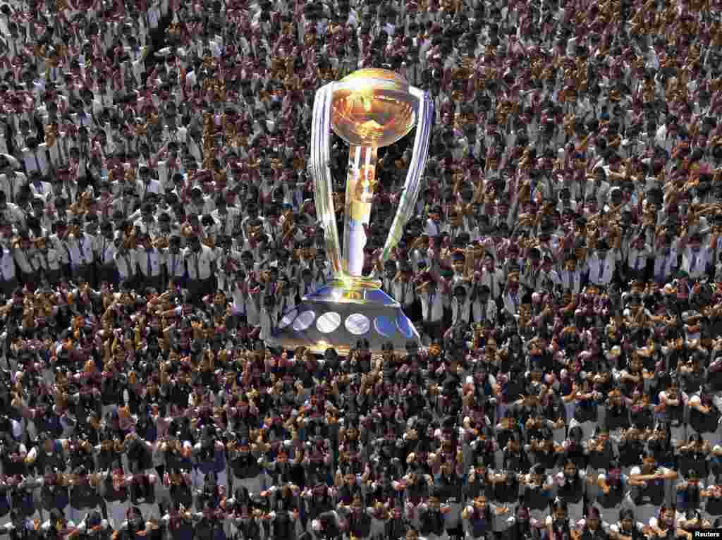Students give thumbs-up to wish the Indian cricket team luck, as they hold a giant cut-out replica of the Cricket World Cup trophy, at a school in the southern Indian city of Chennai.