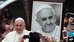 Le pape François vient de passer son portrait alors qu'il arrive à une réunion des jeunes à l'université de Santo Tomas à Manila, Philippines, le 18 janvier 2015.