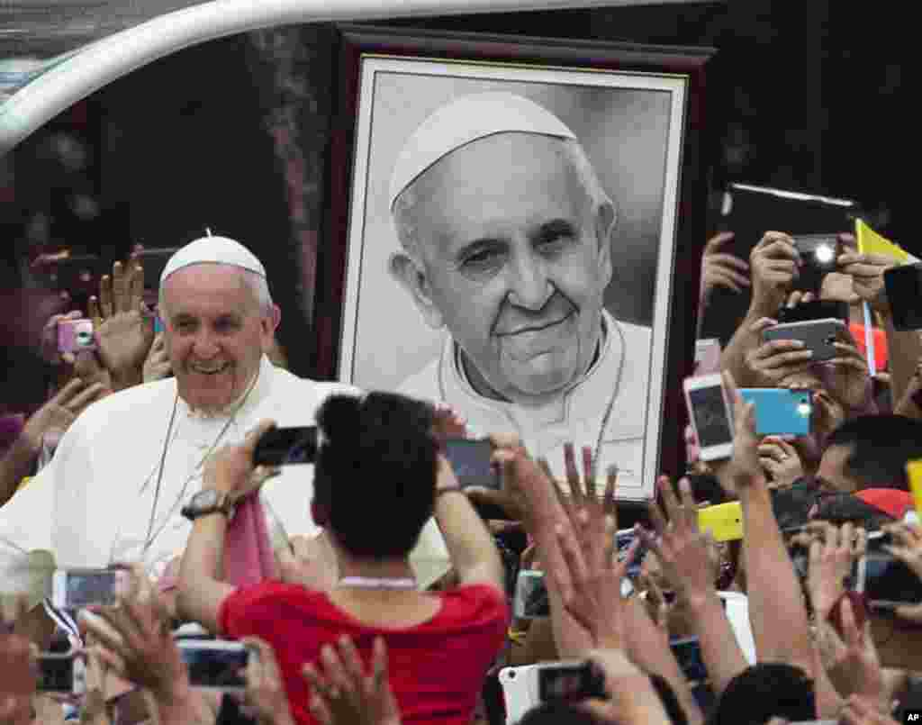 Pope Francis passes a portrait of himself as he arrives to meet youths in Santo Tomas University in Manila, Jan. 18, 2015.