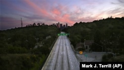 FILE - In this April 26, 2020, file photo, empty lanes of the 110 Arroyo Seco Parkway that leads to downtown Los Angeles is seen during the coronavirus outbreak in Los Angeles, Calif. (AP Photo/Mark J. Terrill, File)