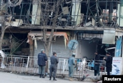 Afghan policemen inspect the site of a suicide bomb attack that killed 105 people and wounded nearly 250 others, in Kabul, Afghanistan, Jan. 28, 2018. The Taliban was quick to claim responsibility.