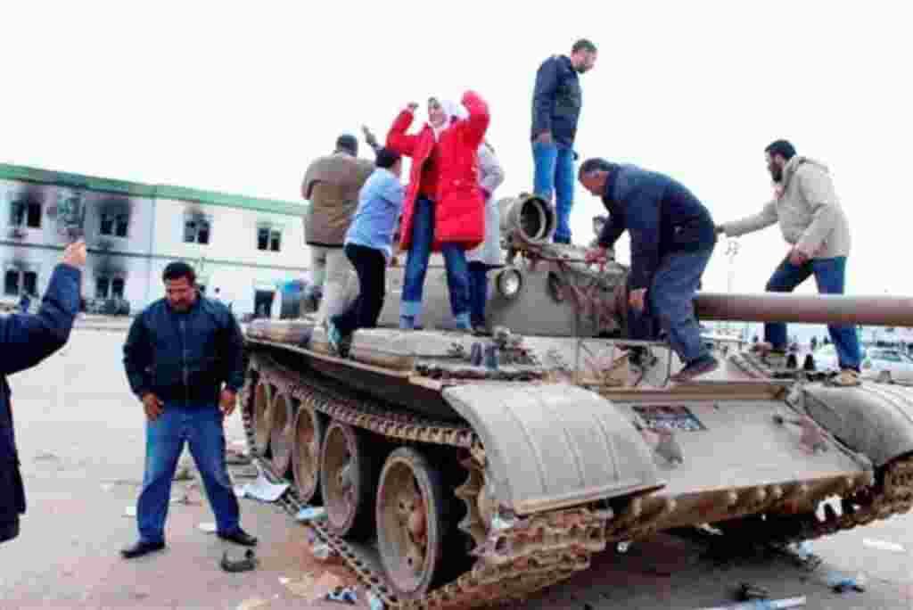 Manifestantes subidos encima de un tanque de als fuerzas armadas.