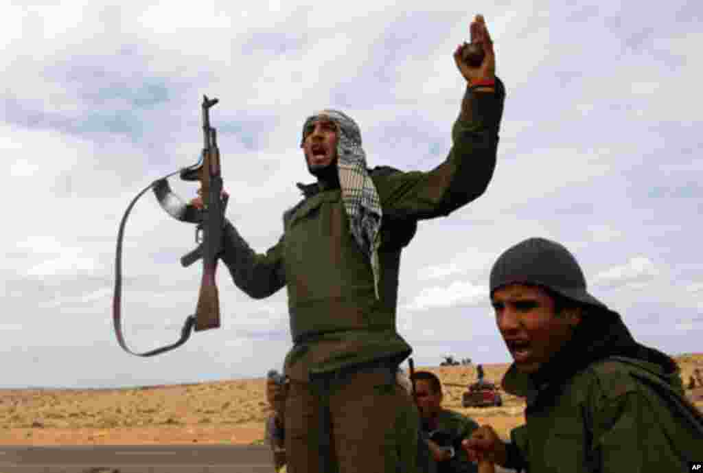 """Rebel fighter shouts """"Allahu Akbar"""" during battle with forces loyal to Libyan leader Moammar Gadhafii on a road between Ras Lanuf and Bin Jawad, March 28, 2011"""