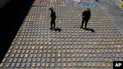 FILE - Police officers walk among packages of seized cocaine at the pacific port of Buenaventura, Colombia, Aug. 10, 2017.