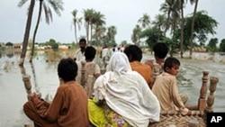 Pakistani villagers make their way through flood waters in Baseera, Pakistan, 24 Aug 2010
