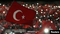 FILE - Supporters of Turkey's President Tayyip Erdogan wave Turkey's national flags as they wait for his speech during a rally against terrorism in Strasbourg, France, Oct. 4, 2015.
