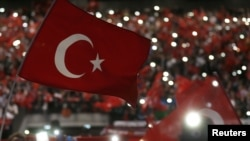 Supporters of Turkey's President Tayyip Erdogan wave Turkey's national flags as they wait for his speech during a rally against terrorism in Strasbourg, France, Oct. 4, 2015.