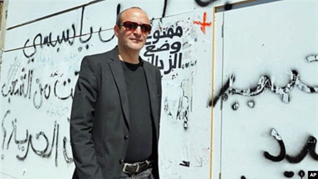 Tunisian director Mourad Cheikh walks past a wall covered with graffiti in Tunis, ahead of the screening of his documentary 'No More Fear' - a 74-minute documentary filmed in the midst of the uprising that led to Tunisian President Zine el Abidine Ben Ali