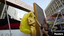 An Oscar statue is uncovered outside the Dolby Theater during preparations leading up to the 87th Academy Awards in Hollywood, California, Feb. 21, 2015.