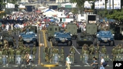 FILE - The military creates a perimeter at a government-subsidized food market in Caracas, Venezuela, Feb. 14, 2004.