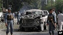 Cảnh sát Afghanistan bên cạnh xác một chiếc xe sau vụ nổ bom tại thành phố Jalalabad ở phía đông thủ đô Kabul, ngày 13/8/2012