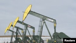 Pompa angguk minyak di lokasi pengeboran minyak milik Hess, dekat Williston, North Dakota, 12 November 2015.