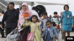 Sebagian dari kloter pertama WNI dari Mesir, berjalan di landasan pacu sesaat setelah turun dari pesawat mereka di Bandara Internasional Soekarno-Hatta, Jakarta, Rabu