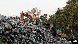 A bulldozer moves piles of garbage in Karantina, east Beirut, Lebanon, Nov. 1, 2015.