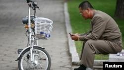 지난 10월 평양 시내에서 한 남성이 자전거를 세워놓고 휴대전화를 사용하고 있다. (자료사진)