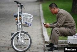 지난 10월 평양 시내에서 한 남성이 자전거를 세워놓고 손전화를 사용하고 있다.